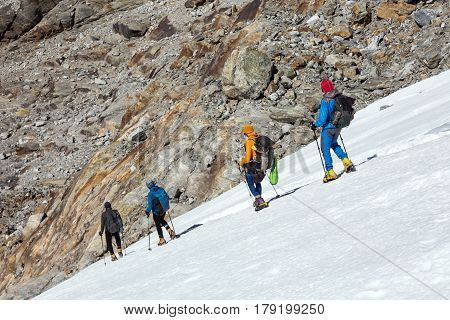 Team of Mountain Climbers carefully stepping down on Glacier using high Altitude Boots and Crampons and other Alpine Gear