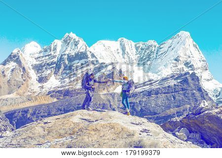 Two People staying on top of Rock and passing Battle of Water Friendship and mutual Support Scene high snowcapped Mountains on Background light toned for text layout.