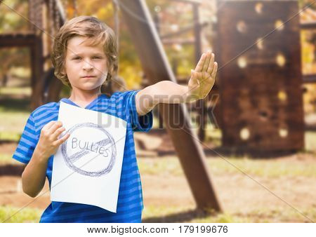 Digital composite of Sad boy holdingn anti bullying sign against playground