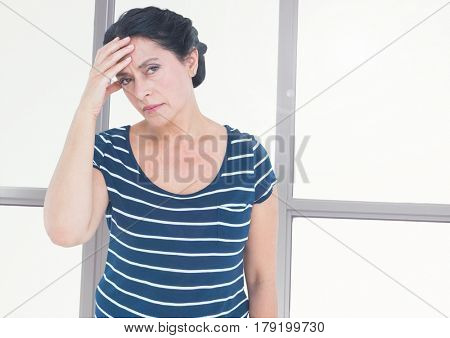 Digital composite of Stressed tired woman in front of windows
