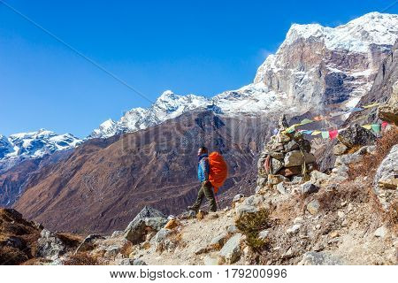View of Himalaya Mountains and Nepalese professional Guide in blue Jacket staying on rocky Slope with red Backpack