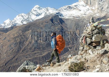 Portrait of Nepalese professional Mountain Guide staying on Footpath and looking up at high Altitude Summits carrying red Backpack and alpine climbing Gear