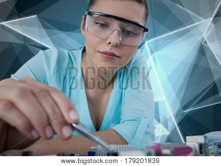 Digital composite of Woman with electronics against blue geometric background