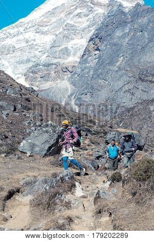 Group of People travelling on Hike in high Mountains Countryside sporty casual Clothing Backpacks and Gear walking on Footpath with snowy severe Walls on Background