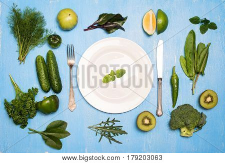 Green vegetables fruit and herbs around white plate and silverware on wooden blue background. Detox and diet concept.