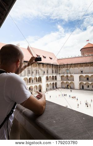 Male traveler on the background of Arcades in Wawel Castle in Cracow. Poland. Renaissance. A man takes photos on his mobile phone from the second floor of the courtyard in Wawel Castle