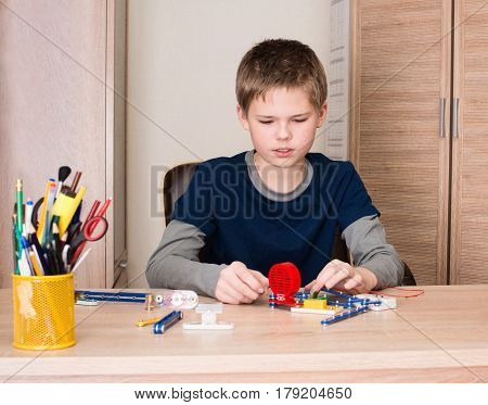 Pre teen boy doing school electronic project in his room at home.