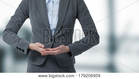 Digital composite of Business woman mid section with hands together in blurry grey office