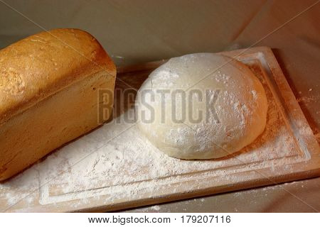 The process of baking. Ingredients. Flour into a bowl with a spoon and eggs in a plate rolling pin whisk strainer spices and milk on a wooden background. Spilling flour chaos confusion