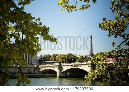 Unusual rare view of Eiffel tower and Pont de la Concorde with a piece of Palais Bourbon to the left on a bright summer day with clear blue sky through maple trees