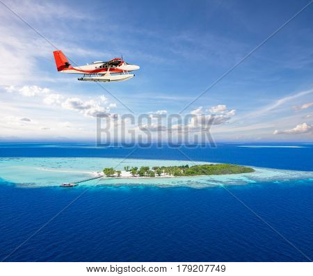Seaplane flying above small tropical island on Maldives, aerial view. Travel, vacation, transportation and beach holiday concept