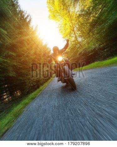 Dark motorbiker riding high power motorbike in nature with beautiful sunrise light, gesturing his hand above head