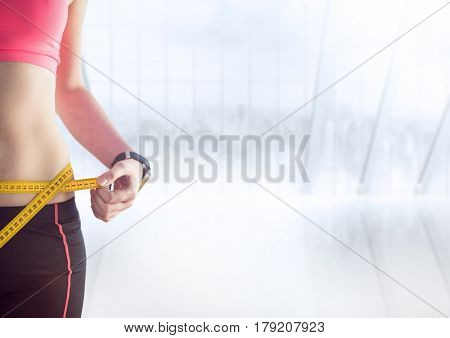 Digital composite of Woman torso with measuring tape against blurry window