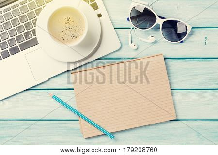 Desk table with laptop, notepad, coffee and sunglasses on wooden table with sun beam. Workplace. Top view with copy space.