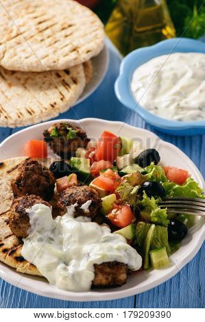 Greek meatballs (keftedes) with pita bread and tzatziki dip.