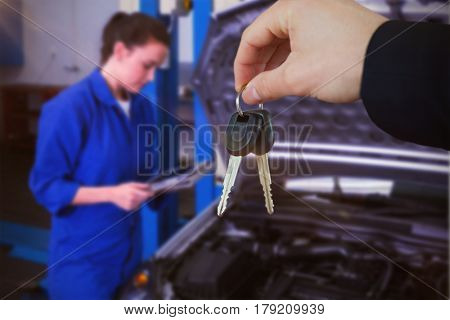 Woman smiling while receiving car keys against mechanic using tablet to fix car