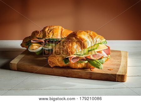 Croissants sandwiches on the wooden cutting board. Selective focus on the front croissant sandwich