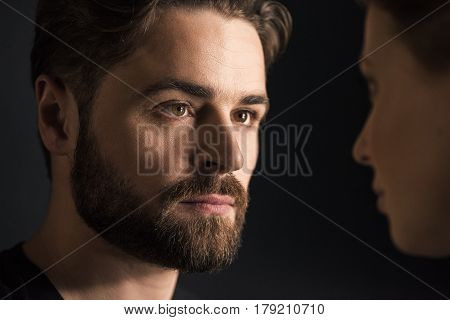 Close-up portrait of young man and woman looking at each other on black