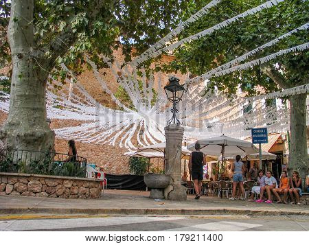 MAJORCA SPAIN - SEPTEMBER 8 2007: People wait beginning of municipal holiday at little town square decorated with festive paper garlands in Majorca Spain on September 8 2007.