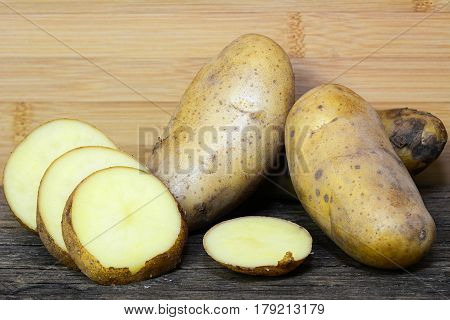 Potatoes and potato sliced on wooden table