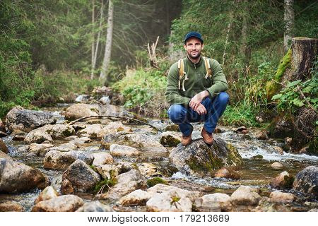 Portrait of a smiling young man wearing a backpack crouching by a river while out for a hike alone in the forest