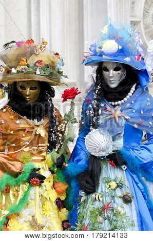 Venice, Italy - February 26th, 2011: Two colorful masks During the carnival parade in Piazza San Marco in Venice, the mask is to be photographed by photographers on the street.