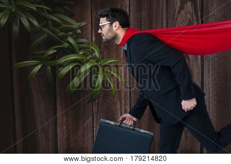 Digital composite of Confident business man super hero walking against wooden background with leaves
