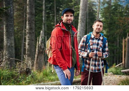 Portrait of two smiling young men in backpacks and hiking gear standing together while out for a hike in the forest
