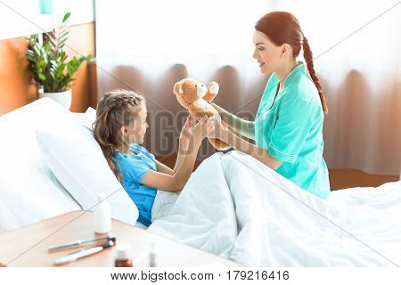 Smiling Girl And Nurse Holding Teddy Bear In Hospital Room