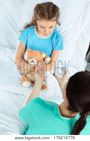 Doctor Giving Pill To Little Patient With Teddy Bear Lying On Bed In Hospital