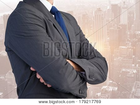 Digital composite of Business man mid section with arms folded against skyline