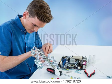 Digital composite of Man with electronics against blue blurry background