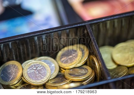 Open cash registrer containing many coins of euro ans banknotes