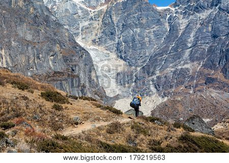 View of heavy loaded Nepalese Porter carrying Mountain Expedition Luggage on Footpath with vertical severe rocky Walls on Background