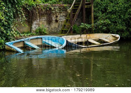 photo of two boats partly under water with reflection in the water