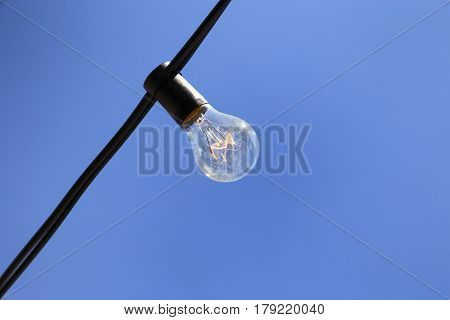 single light bulb on sky background hanging of a wire
