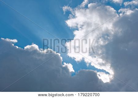 Heaven cloudscape of light white and gray clouds against blue sky with sun beams