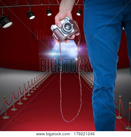 Close up view of man hand holding retro photo camera against view of lights