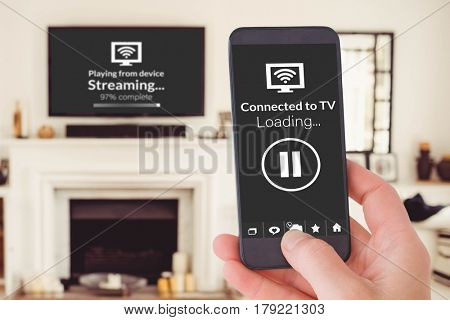 Female hand holding a smartphone against view of living room
