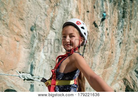 Little Rock Climber in protection climbing Helmet and safety Harness taking self Portrait Picture with high vertical outdoor Wall and other Athletes on Background