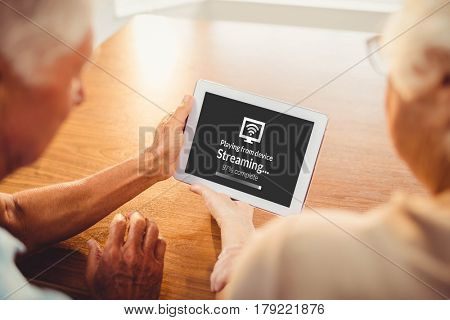 Composite image of text with wi-fi symbol against rear view of senior couple using tablet