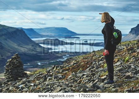 Women travel on a trail in the mountains in Iceland. A woman stands on the edge of the fjord and looks at the landscape towards the fjord and the bay