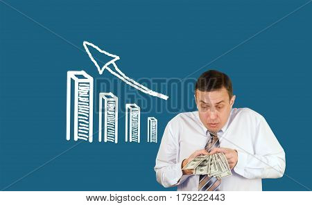 Surprised businessman holds dollars and growing financial profit schedule in his hand