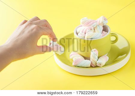 Hand Holding Bowl Of Sweet Marshmallow Pastel Isolated On Yellow Background.
