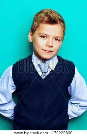 Portrait of a happy smiling seven year old boy in elegant clothes over bright blue background. Kid's fashion. Education. Copy space.