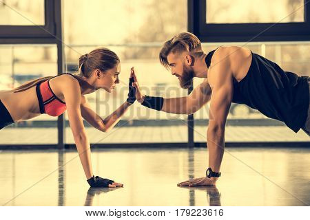 Young Sporty Man And Woman Doing Plank Exercise And Giving High Five