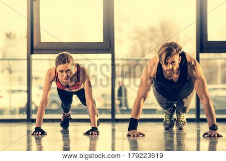 Young Athletic Man And Woman In Sportswear Doing Plank Exercise In Gym