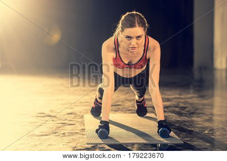 Young Sporty Woman Doing Plank Exercise With Dumbbells