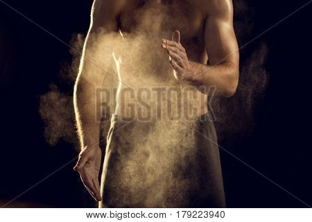 Front View Of Muscular Sweaty Sportsman With Chalk Powder On Black