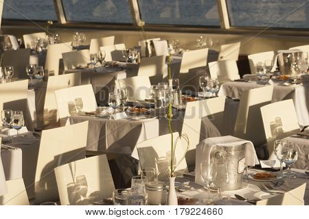 Elegant white place settings on a small dinner cruise boat with tables and chairs.